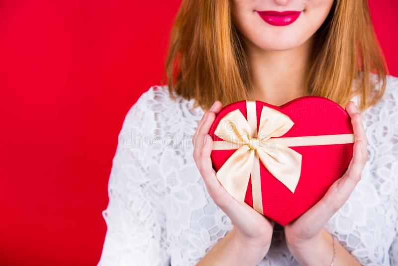 Jonge glimlachende vrouw die rode giftdoos in vorm van hart op Re houden stock foto
