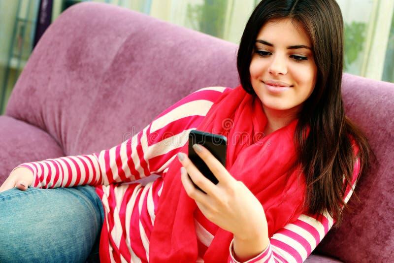 Jonge glimlachende vrouw die smartphone gebruiken stock afbeeldingen