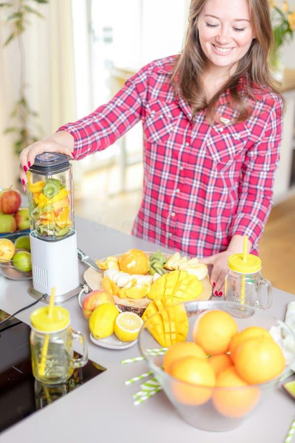 Jonge glimlachende vrouw die smoothie met verse greens in de mixer in keuken thuis maken stock foto