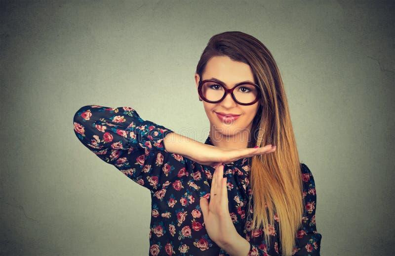 Jonge glimlachende vrouw die tijd uit tonen stock fotografie