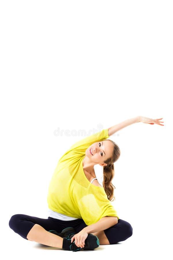 Jonge glimlachende vrouw die uitrekkende oefeningen doen stock foto