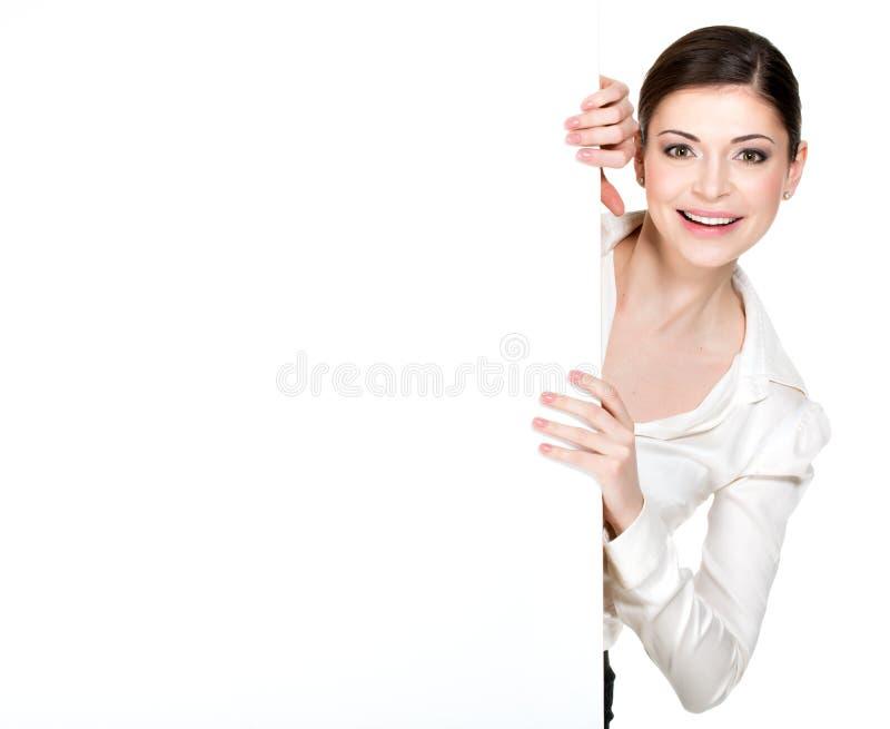 Jonge glimlachende vrouw die van witte lege banner kijken royalty-vrije stock afbeeldingen