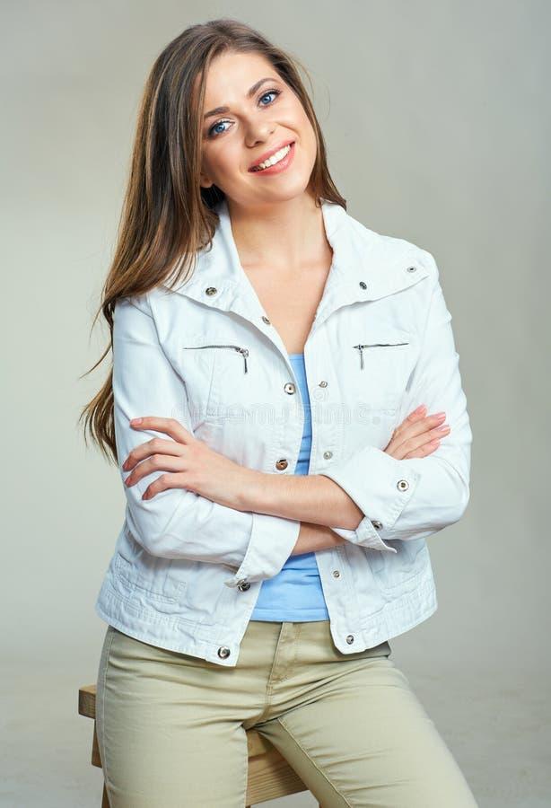 Jonge glimlachende vrouw die witte jasjezitting op barstoel dragen royalty-vrije stock foto's