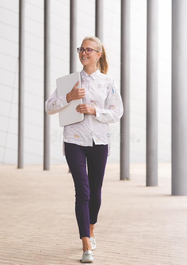 Jonge glimlachende vrouw die witte laptop houden stock fotografie