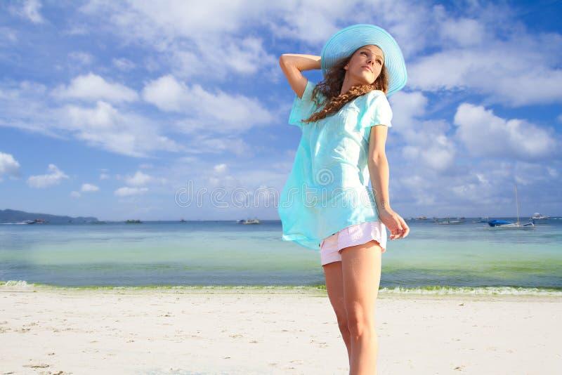 Jonge glimlachende vrouw in hoed op tropische overzeese achtergrond royalty-vrije stock foto's