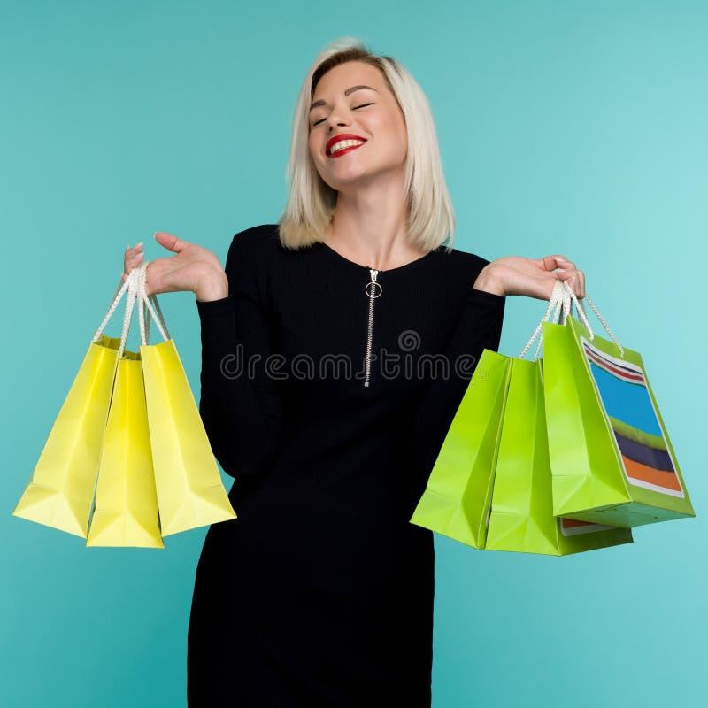 Jonge glimlachende vrouw houdt boodschappentassen vast in zwarte feestdagen Happy Girl op blauwe achtergrond stock foto's