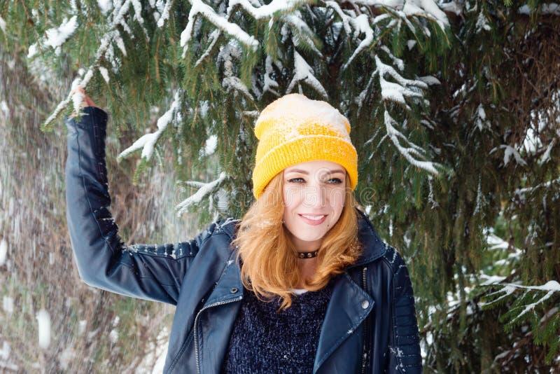 Jonge glimlachende vrouw met blauwe ogen en blond haar in een gele breiende hoed en zwart leerjasje onder de spar stock afbeeldingen