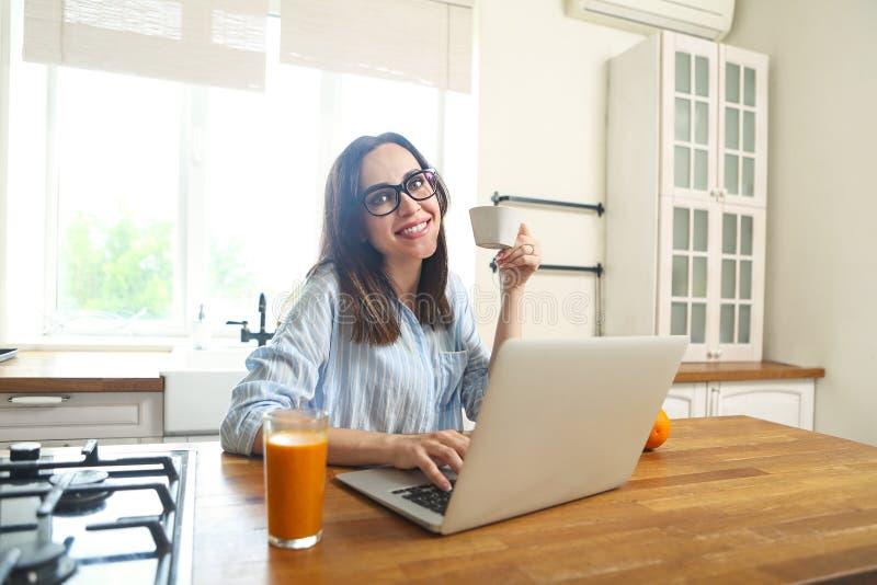 Jonge glimlachende vrouw met computer en kop van koffie bij kitch royalty-vrije stock fotografie