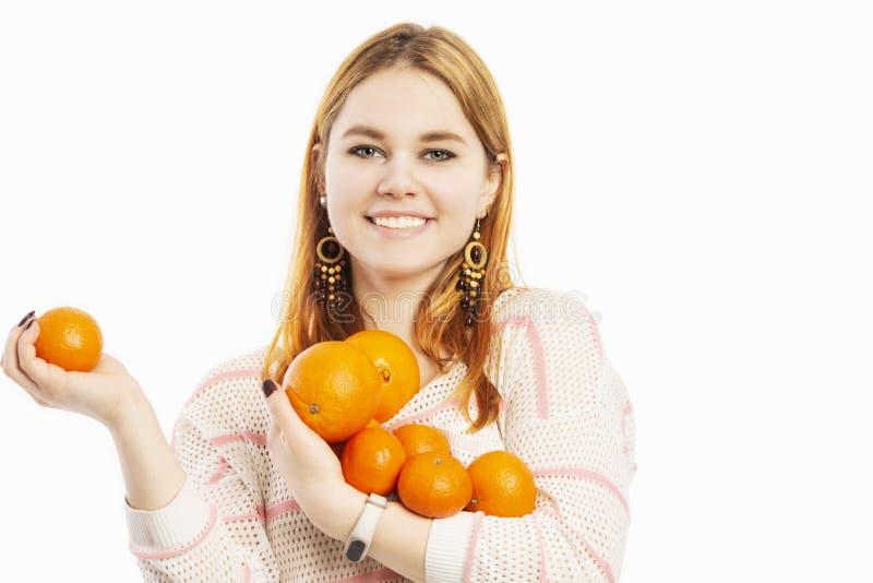 Jonge glimlachende vrouw met een armvol sinaasappelen royalty-vrije stock foto