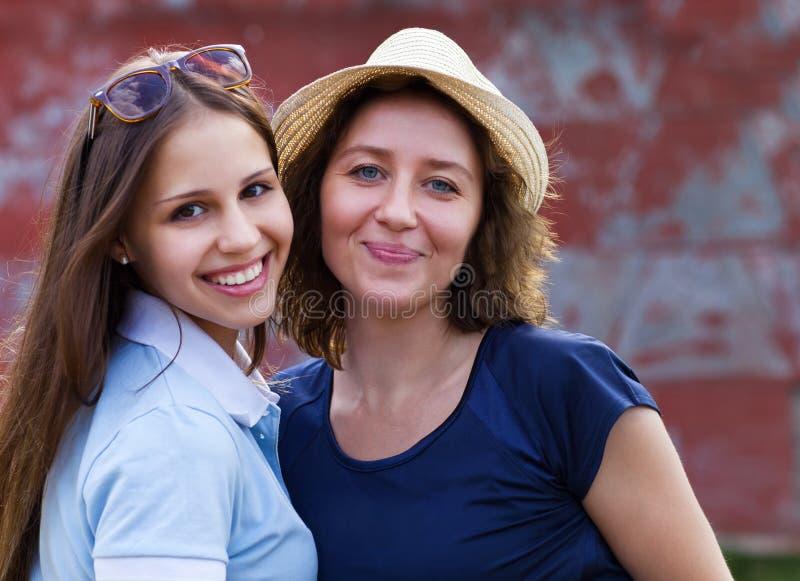 Jonge glimlachende vrouw met haar tienerdochter royalty-vrije stock afbeelding
