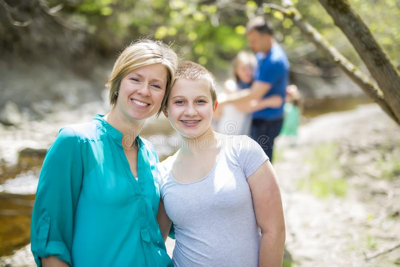 Jonge glimlachende vrouw met haar tienerdochter in openlucht stock afbeeldingen