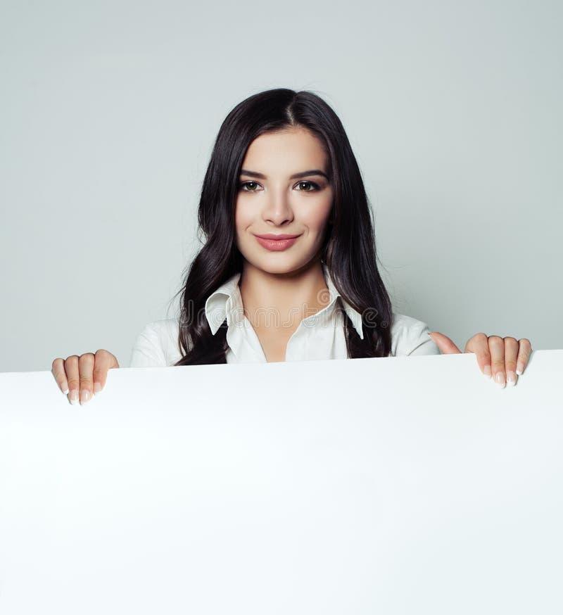 Jonge glimlachende vrouw met witte lege document banner stock foto's