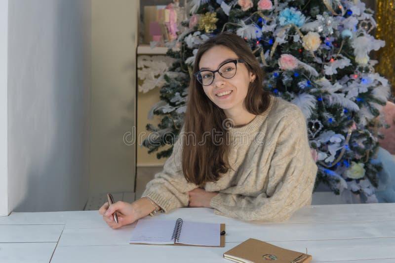 Jonge glimlachende vrouw naast de boom die de camera en het glimlachen bekijken royalty-vrije stock foto
