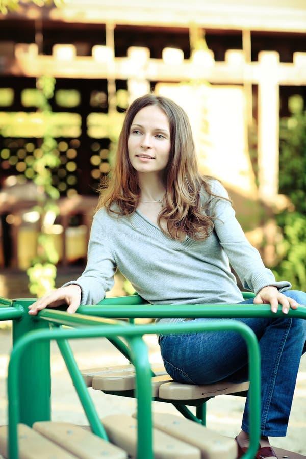 Jonge glimlachende vrouw op carrousel royalty-vrije stock afbeeldingen