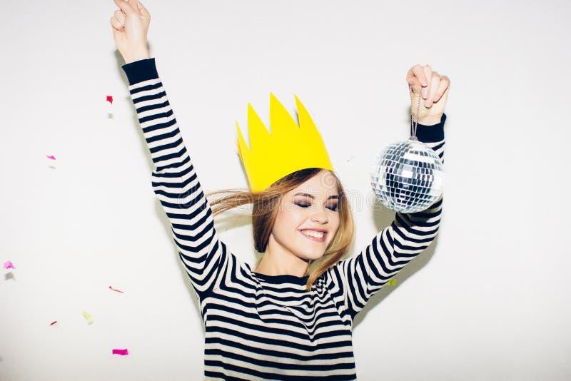 Jonge glimlachende vrouw op witte vierende partij als achtergrond, die gestripte kleding en gele document kroon, gelukkige dynami royalty-vrije stock foto