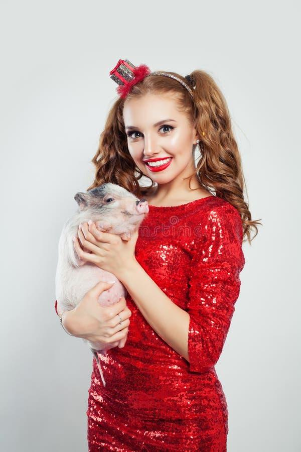 Jonge glimlachende vrouw in rode manierkleding met weinig varken op witte achtergrond royalty-vrije stock foto