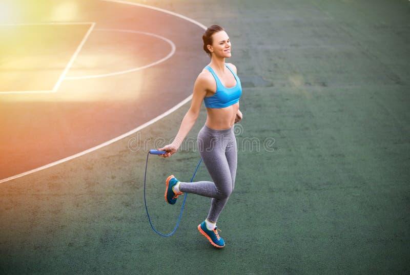 Jonge glimlachende vrouw in sportkleding opleiding met touwtjespringen stock afbeeldingen