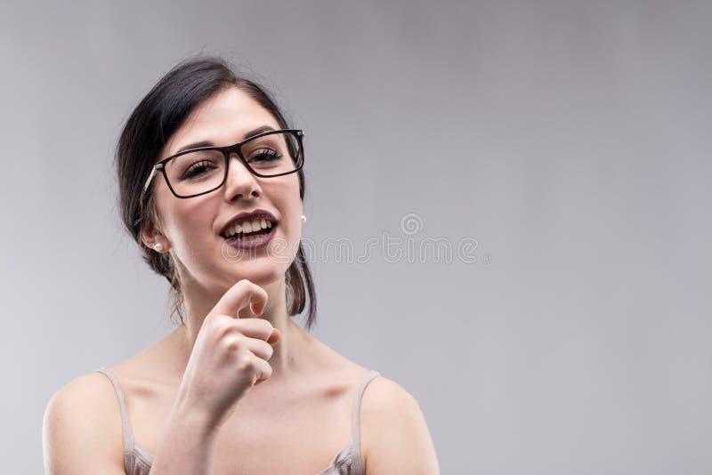 Jonge glimlachende vrouw tegen grijze achtergrond stock afbeeldingen
