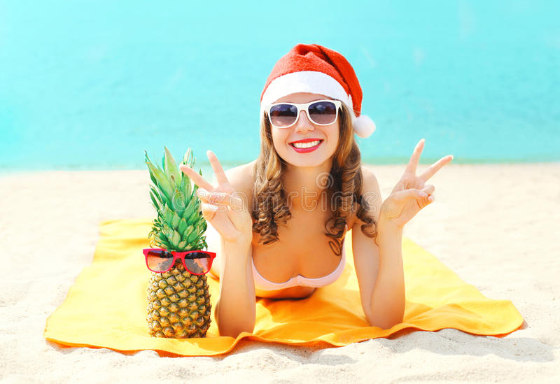 Jonge glimlachende vrouw van het Kerstmisportret de vrij in rode santahoed en ananas die op strand over overzees liggen royalty-vrije stock afbeeldingen