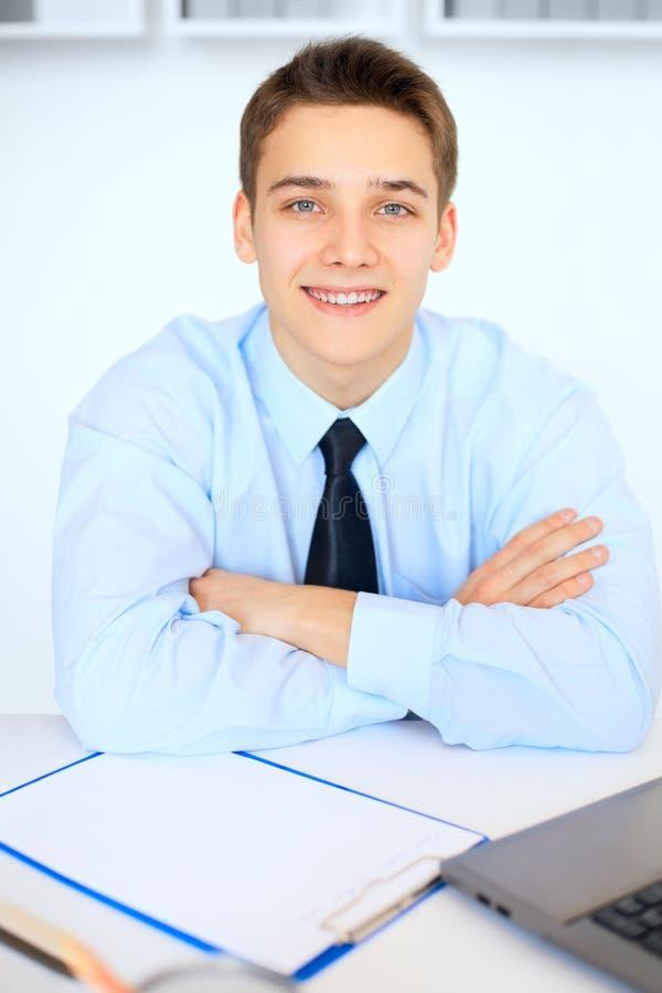Jonge glimlachende zakenman in bureau royalty-vrije stock afbeelding
