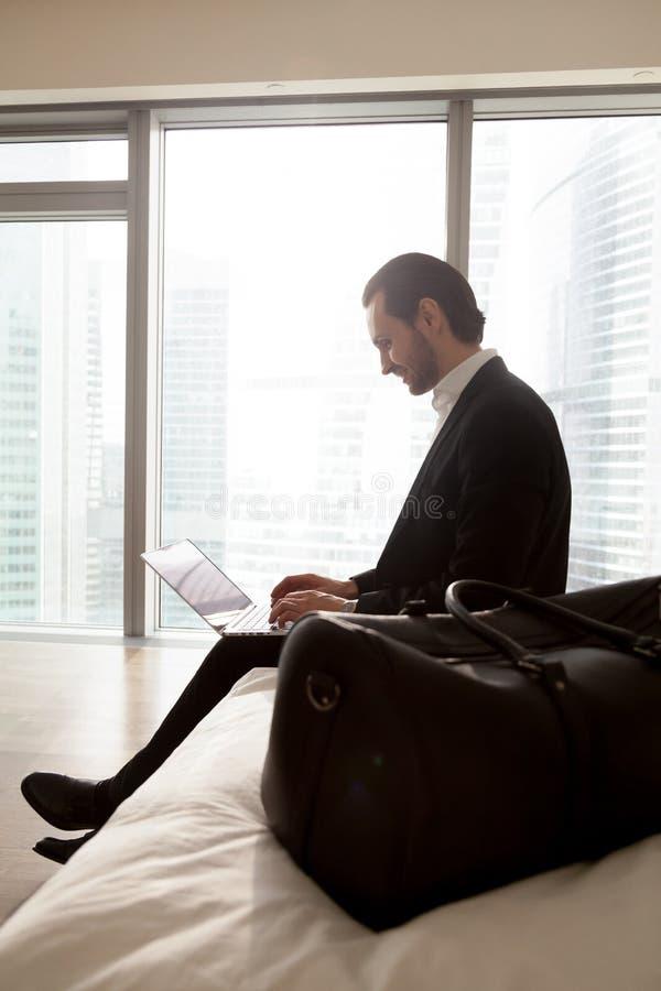 Jonge glimlachende zakenman die aan laptop in slaapkamer werken royalty-vrije stock fotografie