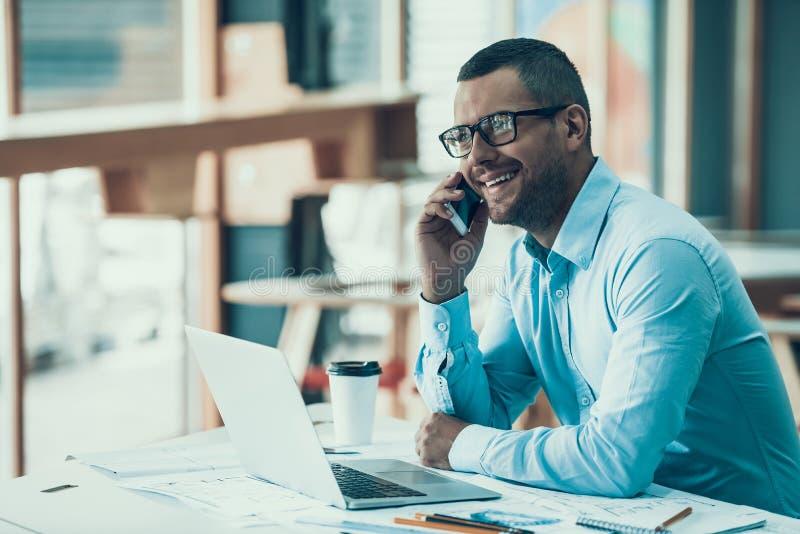 Jonge glimlachende zakenman die in bureau werken royalty-vrije stock afbeelding