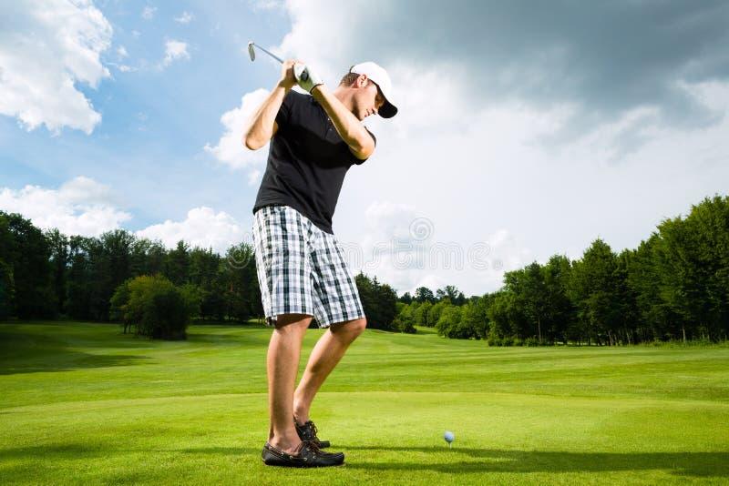 Jonge golfspeler op cursus die golfschommeling doet stock afbeeldingen
