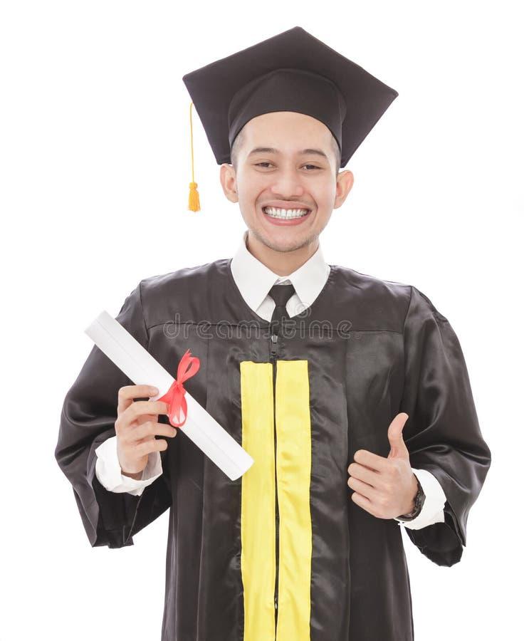 Jonge graduatiemens die terwijl het houden van diploma en het geven van Th glimlachen stock foto's