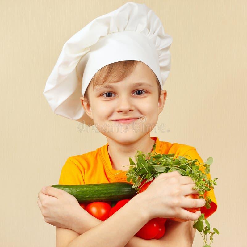 Jonge grappige chef-kok met verse groenten stock foto