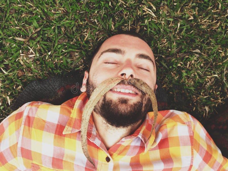 Jonge Grappige Gebaarde Hipster-Mens die op de grond met Snor leggen die van Autumn Long Leaves op Zijn gezicht wordt gemaakt stock afbeelding