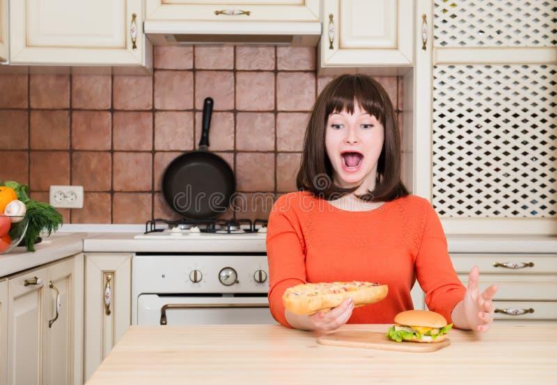Jonge grappige hongerige vrouw die met open mond troep snel voedsel i eten stock foto
