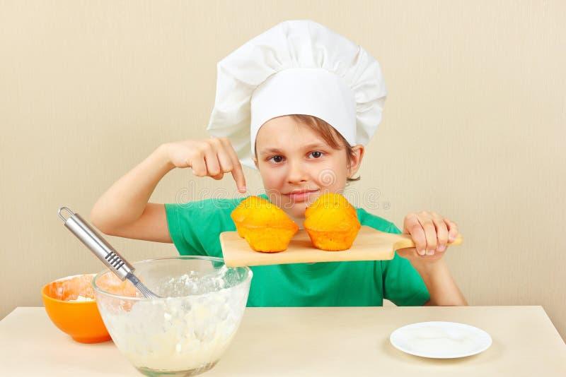 Jonge grappige jongen in chef-kokshoed met een gekookte smakelijke cake stock afbeeldingen
