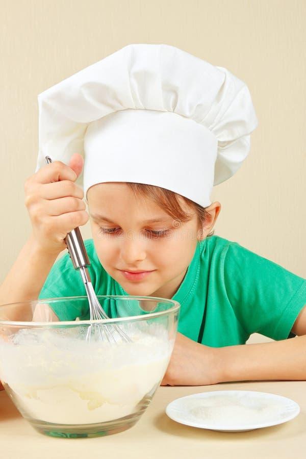 Jonge grappige jongen in de schuifelgangdeeg van de chef-kokshoed voor bakselcake royalty-vrije stock foto