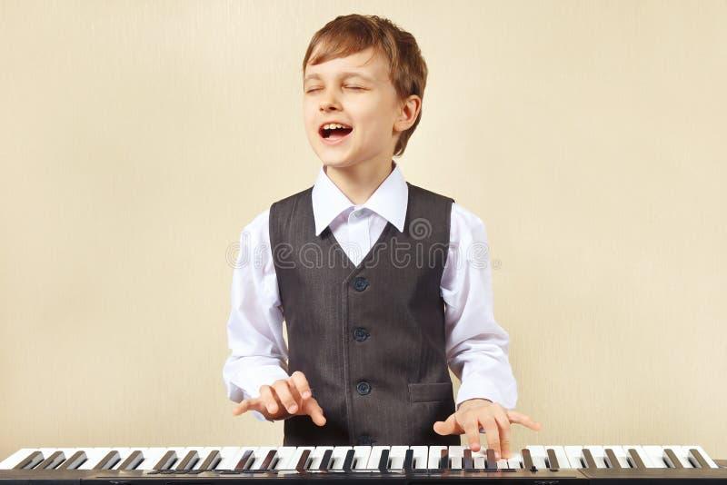 Jonge grappige jongen die in kostuum het elektronische orgel spelen royalty-vrije stock fotografie