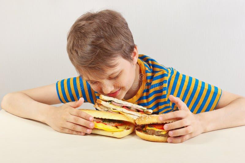 Jonge grappige jongen in een gestreept overhemd bij de lijst met hamburgers en sandwich royalty-vrije stock foto