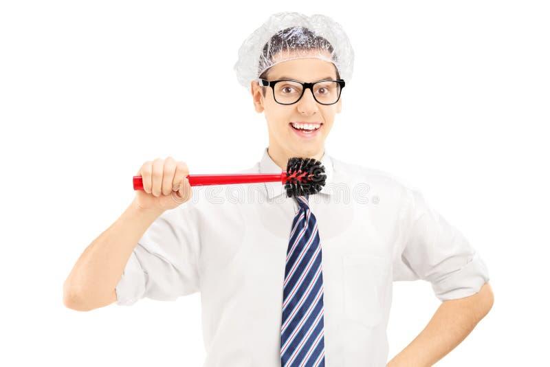 Jonge grappige mens die een toiletborstel houden ongeveer om zijn tanden schoon te maken stock afbeelding