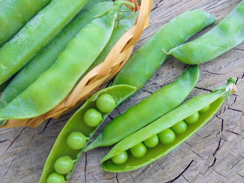 Jonge groene erwten in peulen in een mand op een houten oppervlakte royalty-vrije stock foto