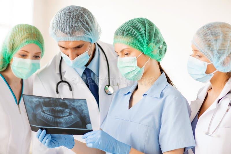 Jonge groep artsen die röntgenstraal bekijken stock foto