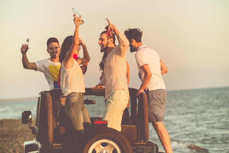 Jonge groep die pret op het strand hebben en in een convertibele auto dansen stock afbeeldingen