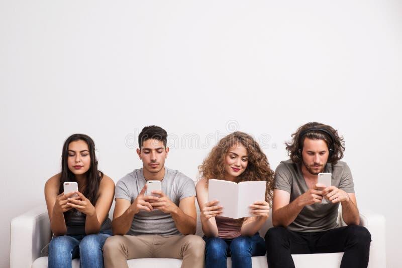 Jonge groep vrienden die moderne technologie gebruiken en traditionele bron van informatie stock afbeeldingen