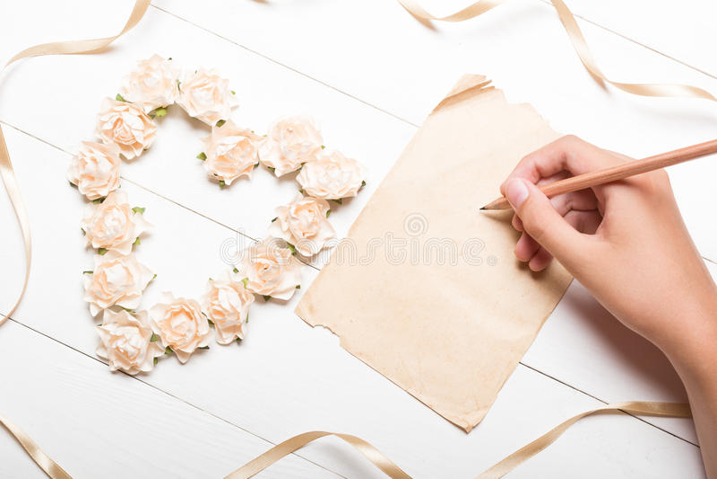 Jonge hand die op document blad schrijven Hart van rozen wordt gemaakt die stock afbeeldingen
