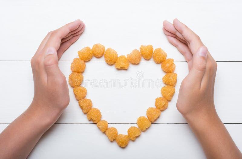 Jonge handen die hart houden die van gele frambozen wordt gemaakt royalty-vrije stock fotografie