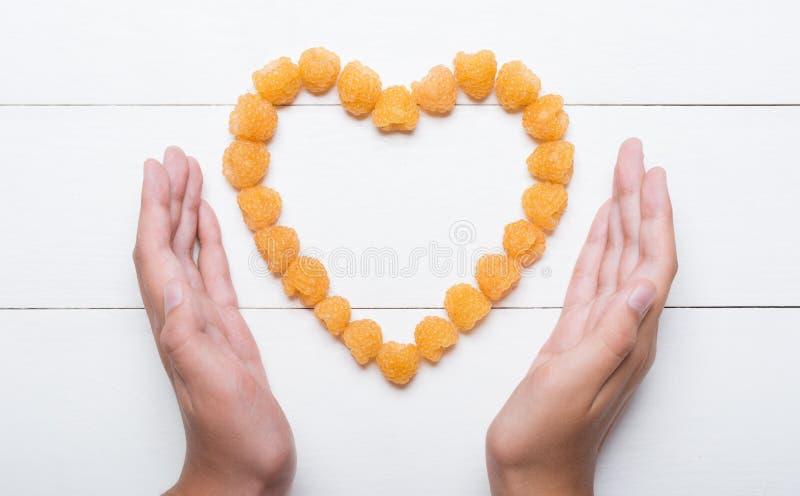Jonge handen die hart houden die van gele frambozen wordt gemaakt royalty-vrije stock afbeelding