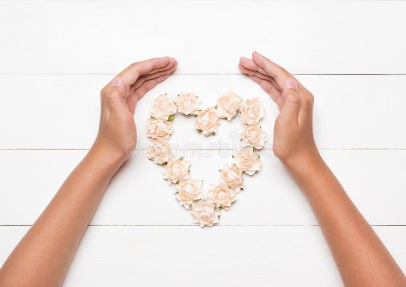 Jonge handen die hart houden die van rozen wordt gemaakt stock afbeeldingen