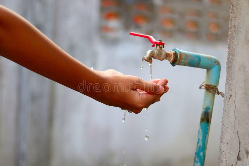 Jonge handen die water met palmen van een oude langzame stromend waterkraan verzamelen met groot geduld - watertekort - sparen wa stock afbeeldingen