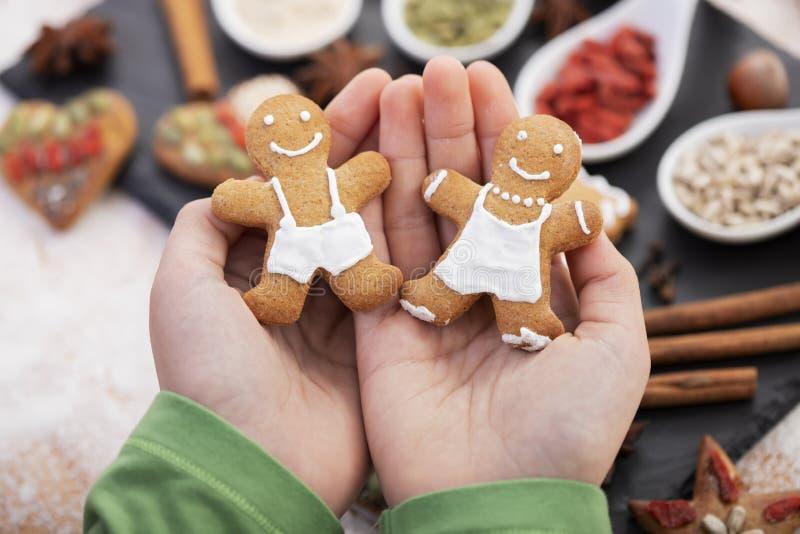 Jonge handen houden van een paar koekjeskoekjes - kerstsnoepjes stock afbeelding
