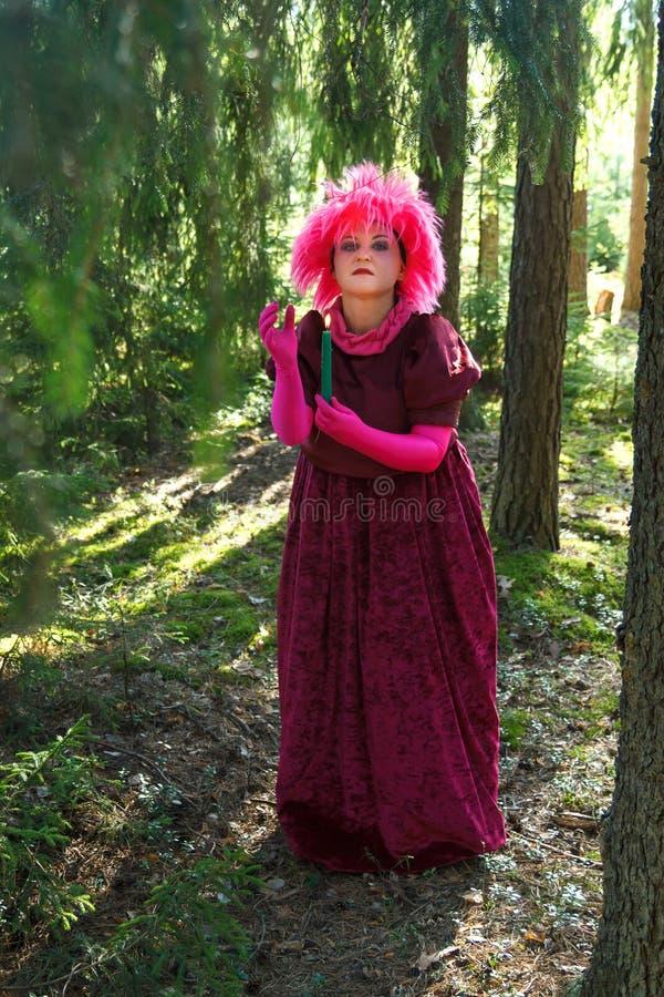 Jonge heks in paarse kleren in het bos met een kaars in zijn hand royalty-vrije stock afbeelding