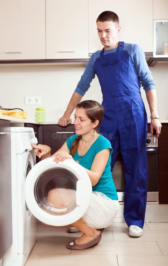 Jonge hersteller die een wasmachine voor huisvrouw in h herstellen royalty-vrije stock foto