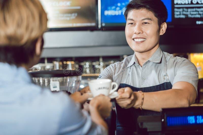 Jonge het glimlachen barista dienende koffie aan klant royalty-vrije stock afbeelding