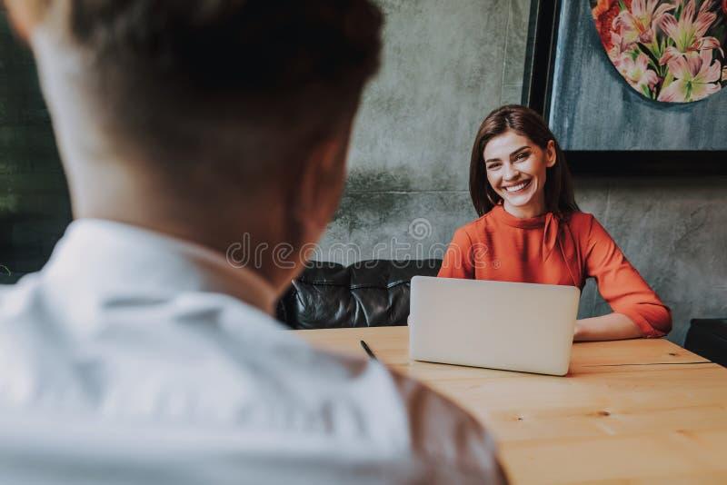 Jonge het glimlachen bedrijfsvrouwenzitting in bureau stock afbeeldingen